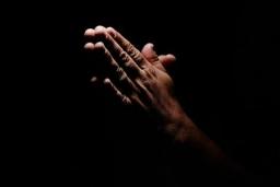48474230-praying-hands-in-black-background.jpg